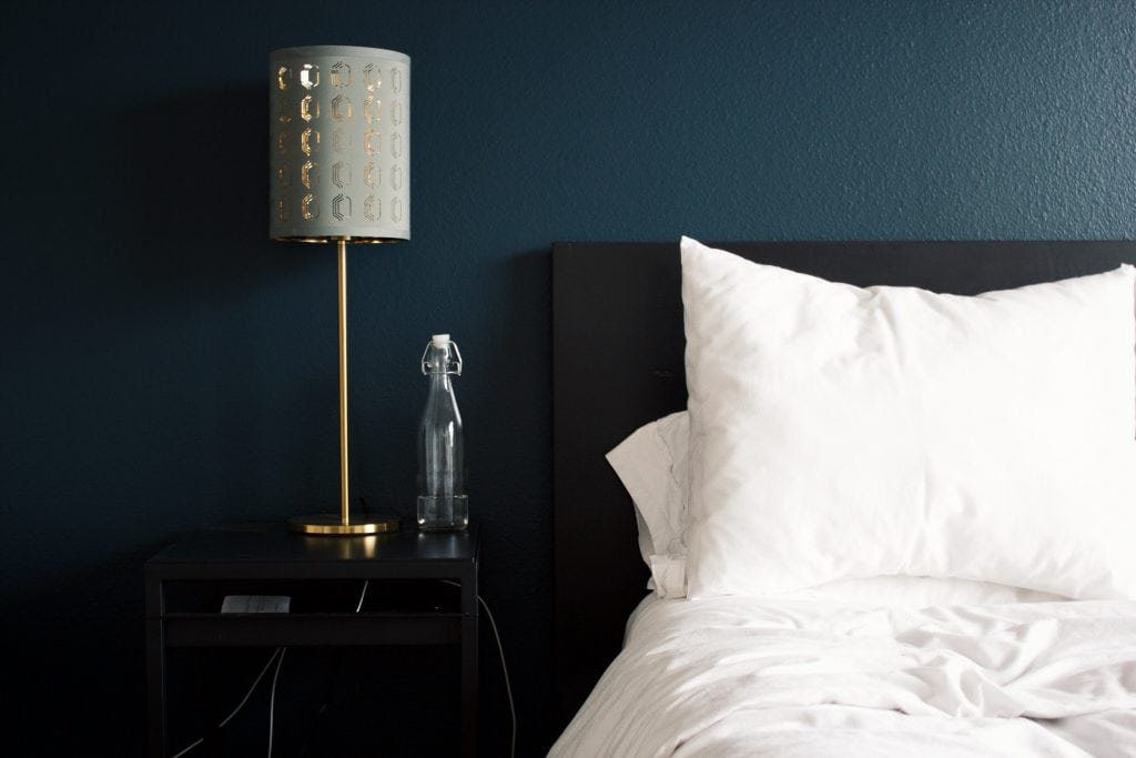 Bedroom with white bed, silver lamp and statue on nightstand. Showing how to get better sleep.