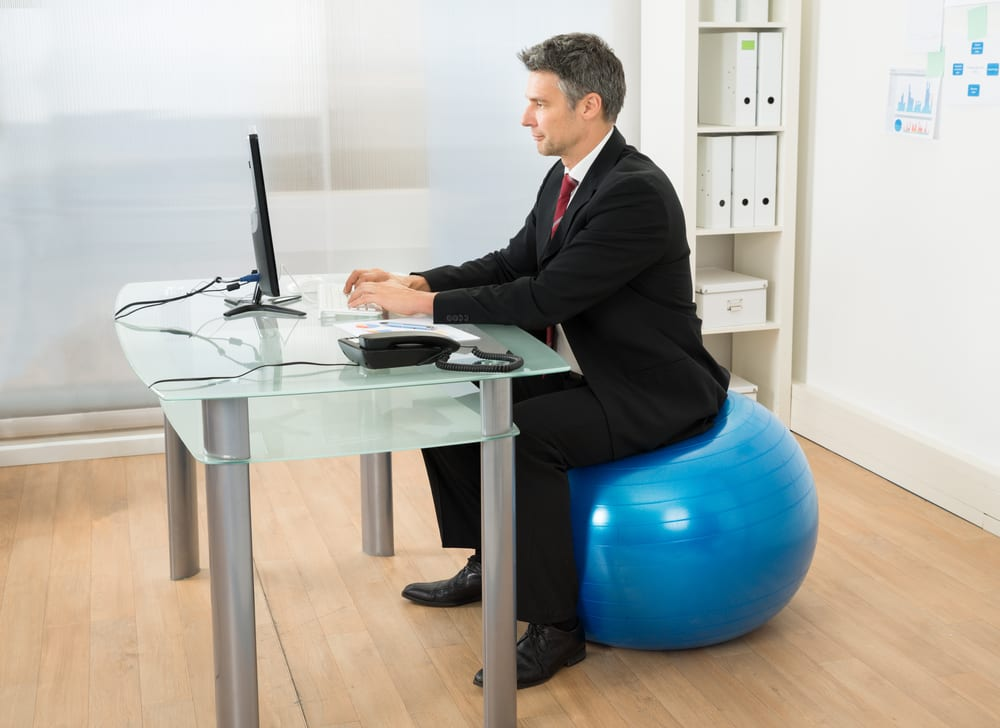 Office worker sitting on an exercise ball as a way to get healthier